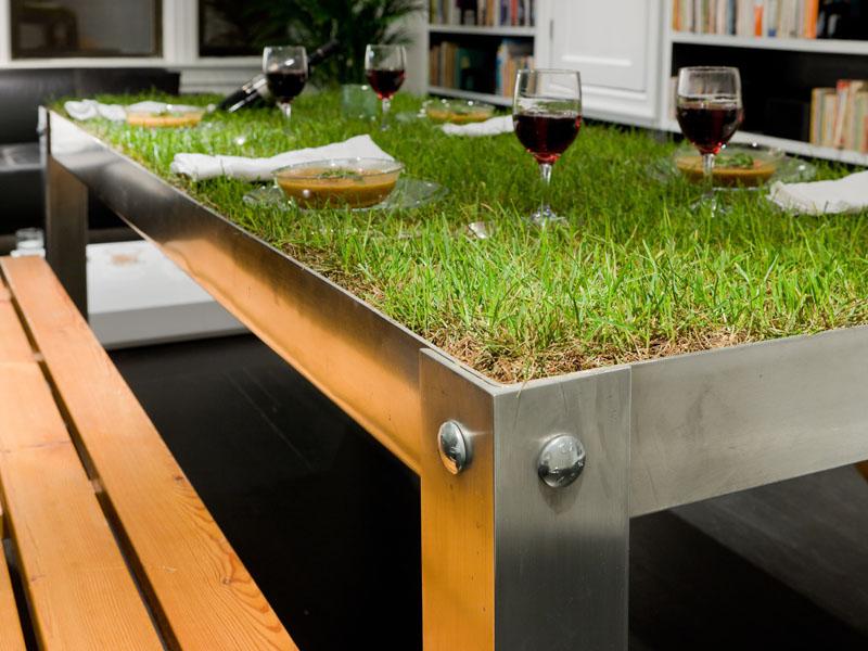 Frontaufnahme des begrünten Tisches, auf dem Teller und Weingläser stehen.
