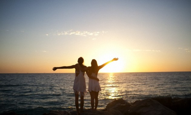 Two young girls holding each other with arms out wide to the sea.